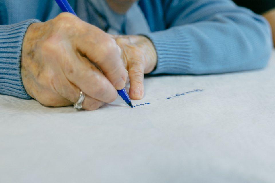 Une dame âgée écrit quelque chose sur un papier, à Neuchâtel